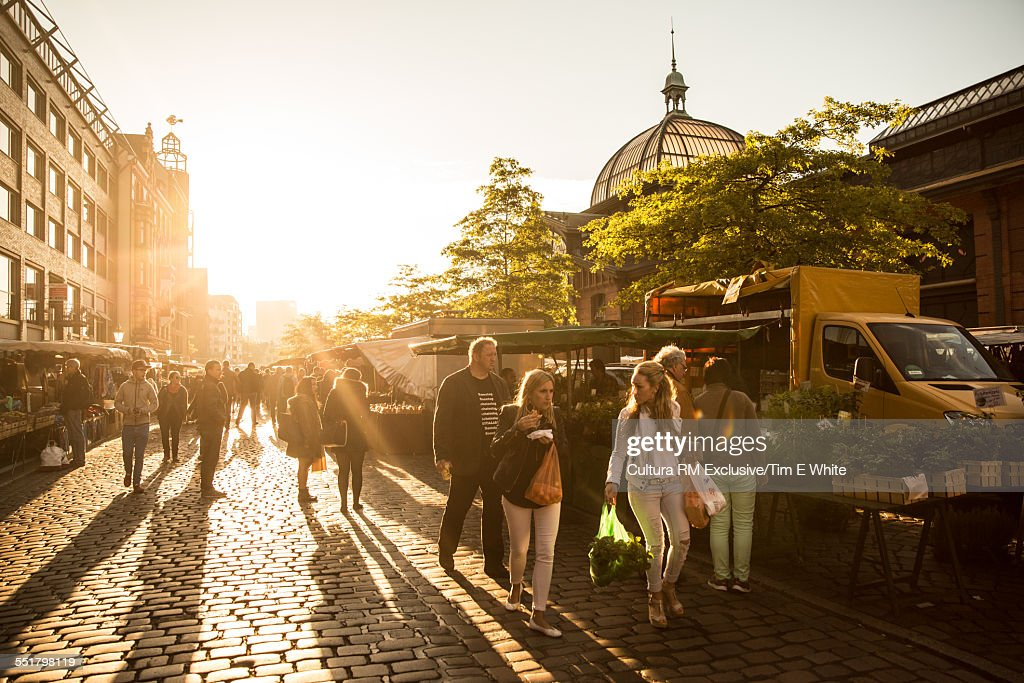 Tourists strolling in fish market at sunrise, Hamburg, Germany