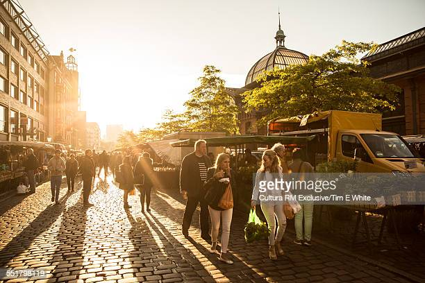 Tourists strolling in fish market at sunrise, Hamburg, Germany
