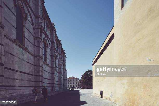 Tourists strolling in shadow of Lucca cathedral, Lucca, Tuscany, Italy