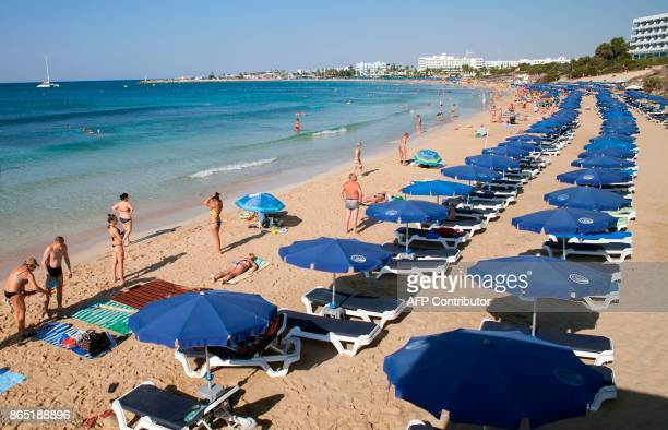 Tourists sunbath at the beach in the resort town of Ayia Napa in southeastern Cyprus on September 7 2017 With more visitors heading to the...