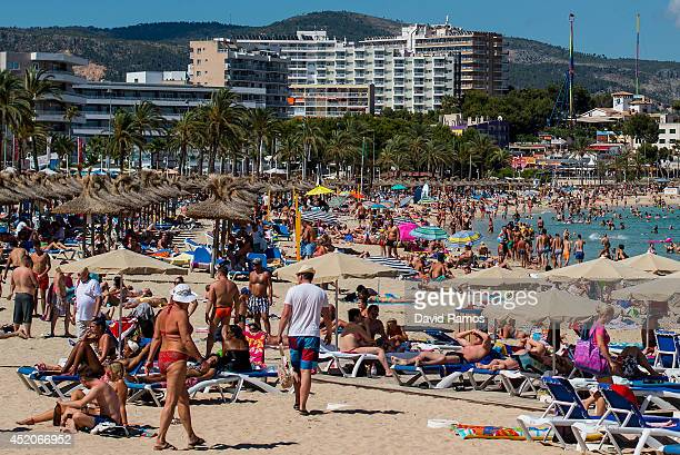 Tourists sunbathe at Magaluf beach on July 12 2014 in Mallorca Spain Magaluf is one of the Britain's favorite holiday destinations popular with sun...