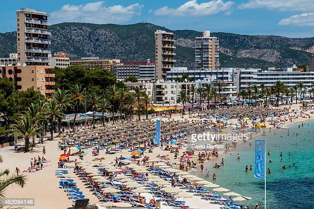 Tourists sunbathe at Magaluf beach on July 13 2014 in Mallorca Spain Magaluf is one of the Britain's favorite holiday destinations popular with sun...