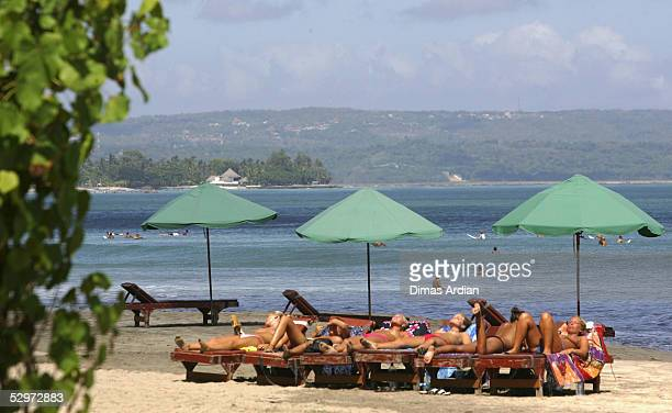 Tourists sunbathe on Kuta Beach on May 24 2005 in Bali Indonesia Australian travel agents have threatened to stop promoting Bali as a destination if...