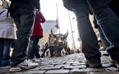 Tourists surround a bull statue in the Financial District near the New York Stock Exchange in New York US on Friday Dec 18 2009 US stocks rose...