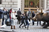 Tourists surround a bull statue stands in the Financial District near the New York Stock Exchange in New York US on Friday Dec 18 2009 US stocks rose...
