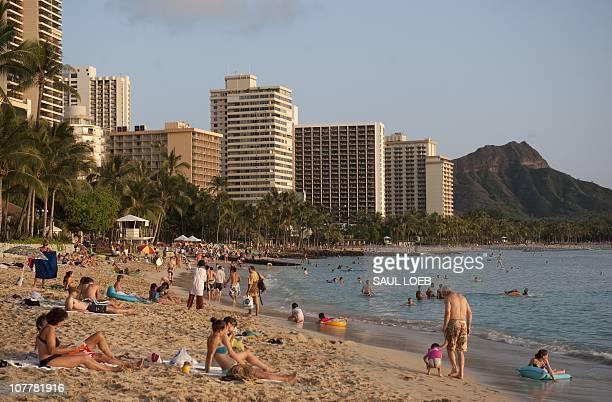 Tourists swim sunbathe and relax along Waikiki Beach in Honolulu Hawaii on December 24 2010 The beach on the south shore of the island of Oahu has...