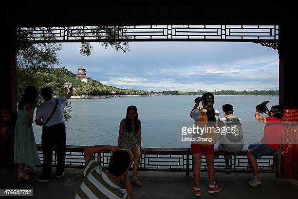 Tourists take a photo beside Kunming Lake at the Summer Palace on June 11 2015 in Beijing China Located on the northwest outskirts of Beijing the...