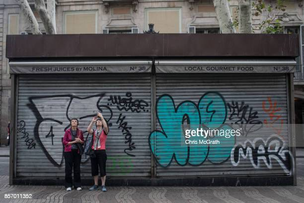 Tourists take a photo in front of a closed shop on Barcelona's famous La Rambla street during a regional general strike to protest against the...