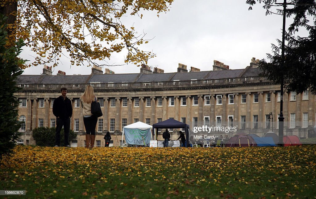 Tourists take a photograph as Campaigners from the Occupy Bath protest group gather in front of Bath's Grade 1 Royal Crescent on November 17, 2012 in Bath, England. The small group of local representatives of the Occupy movement - which staged an occupation in the city for six weeks last year - moved into Royal Victoria Park in front of the historic landmark on Friday night, but claimed they would end the protest on Sunday.