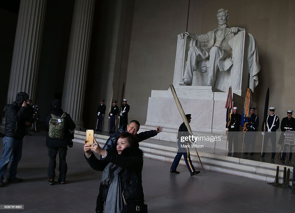 Tourists take a picture before a wreath laying ceremony at the Lincoln Memorial, February 12, 2016 in Washington, DC. The Military District of Washington held a Presidential full honor wreath laying ceremony to commemorate Abraham Lincoln's 207th birthday.