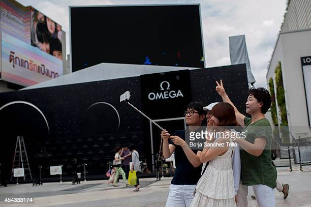 Tourists take a picture with a selfie stick at Siam on August 29 2014 in Bangkok Thailand Thai government has approved a regulation that allows...