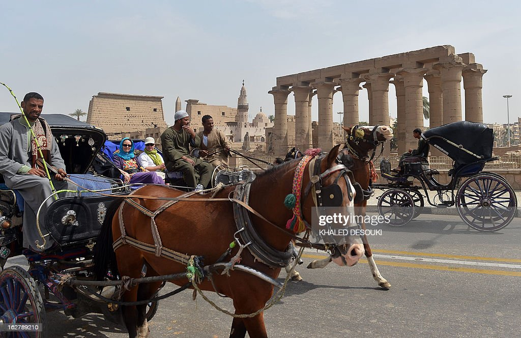 Tourists take a ride in a horse and carriage past Luxor temple, in the Egypt's ancient temple city on February 27, 2013, a day after a hot air balloon exploded and plunged to earth near the city during a sunrise flight, killing up to 19 tourists, including Asians and Europeans, sources said. An initial probe into the hot air balloon crash has ruled out any criminal activity as a cause of the accident, state media said.