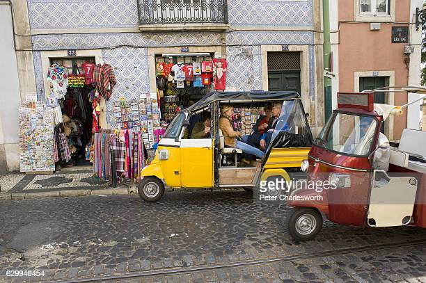Tourists take a ride in threewheeler tuktuks copied from India or Thailand around the small cobbled streets of Lisbon They are passing by a tourist...