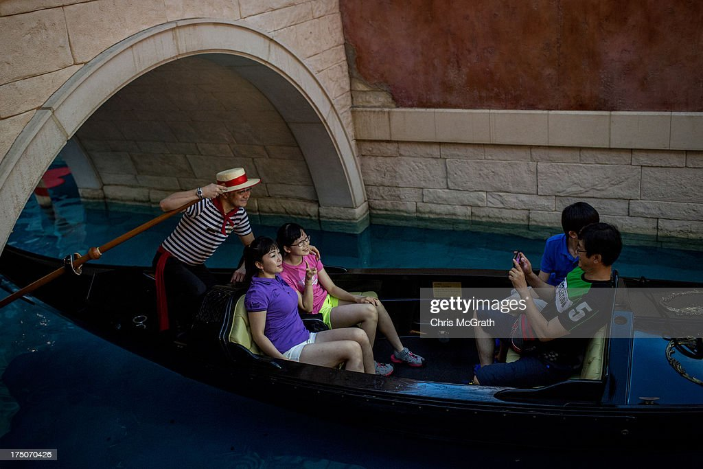 Tourists take a ride on a gondola up the man-made canal inside the Venetian Casino and Hotel on July 29, 2013 in Macau, Macau. Macau, the only place in China with legalized casino gambling is booming. Gambling has been legal in Macau for more than 150 years but has seen a rapid transformation over the last decade from the small time gambling clubs, gangs and prostitution of the 1990s, to becoming the worlds gambling mecca. Last year, Macau generated $38 billion in casino revenue, six times more than Las Vegas, Nevada. Situated just one hour from mainland China and Hong Kong, Macau also known as 'The Oriental Las Vegas ' received 14.1million visitors for the first six months of this year, in the most recent Statistics and Census Bureau report, with close to 90% of visitors being from mainland China, Taiwan and Hong Kong. Although the gambling industry has improved general living standards across Macau, it is not without it's downside. With the influx of big money also comes, higher living costs, with some residents saying issues such as transportation, health care and social welfare have largely been ignored. Property prices have increased dramatically, forcing many small and mid-sized businesses into bankruptcy and pushing some residents to share accommodation or move away completely.