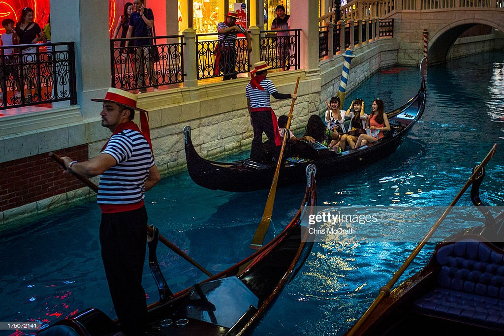 Tourists take a ride on a gondola up the manmade canal inside the Venetian Casino and Hotel on July 29 2013 in Macau Macau Macau the only place in...