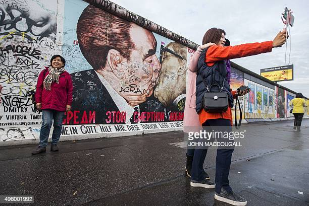 Tourists take a selfie and pose in front of the graffiticovered mural painting 'My God Help Me to Survive This Deadly Love' by Russian painter Dmitri...
