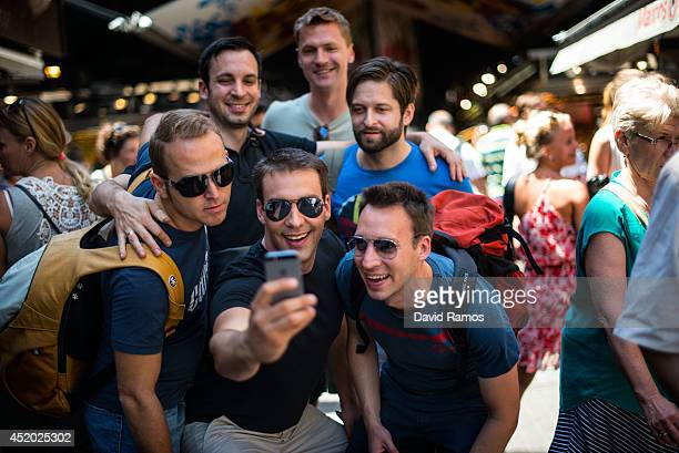 Tourists take a 'selfie' as they visit 'La Boqueria' green market on July 11 2014 in Barcelona Spain As traders of 'La Boqueria' complain about tour...