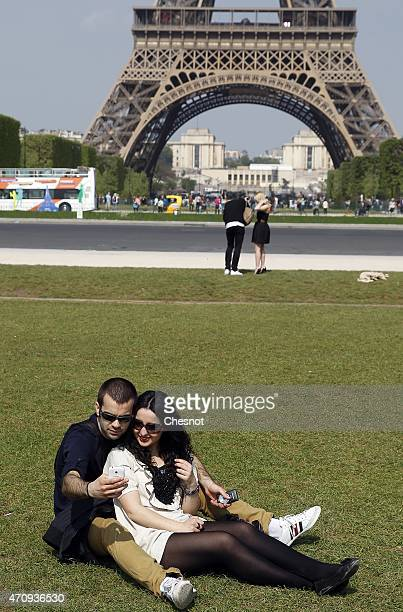 Tourists take a selfie in front of the Eiffel tower on April 24 2015 in Paris France France is still one of the leading tourist destinations in the...