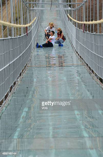 Tourists take a selfie on a suspension bridge made of glass at the Shiniuzhai National Geological Park on September 24 2015 in Pingjiang County China...