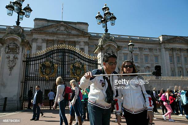 Tourists take a selfie photograph in front of Buckingham Palace using a selfie stick on April 7 2015 in London England Parts of Britain basked in...