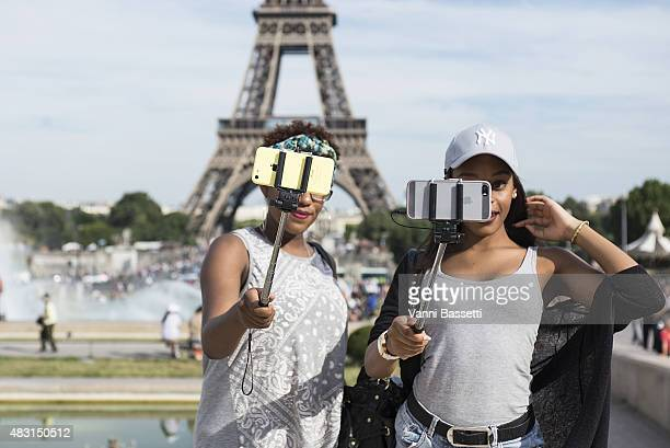Tourists take a selfie using a selfie stick in front of the Eiffel Tower on August 6 2015 in Paris France Using a selfie stick has become a more and...