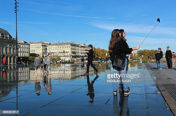 Tourists take a selfie with a stick on the water mirror in Bordeaux on October 31 2015 as the weather forecast predicts a weekend with higher...