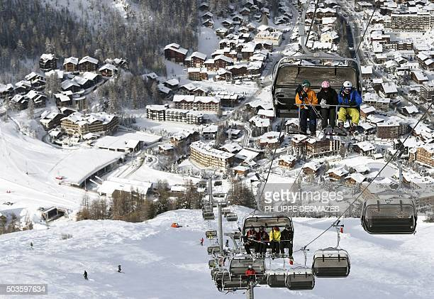 Tourists take a ski lift in the French ski resort of Val d'Isère in the Central French Alps on January 6 after snowfall during the last few days /...
