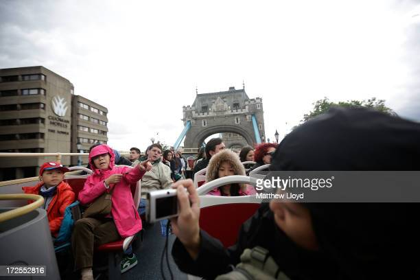 Tourists take an open top bus trip around London in grey cloudy weather on July 3 2013 in London England Britain is experiencing an unusually wet...