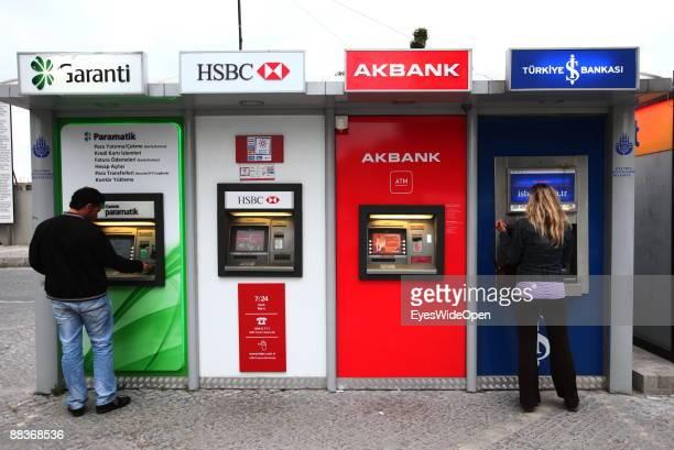 Tourists take cash at a Cashmachine of Garanti HSBC AKBANK TUERKIYE BANKASI on May 20 2009 in Istanbul Turkey
