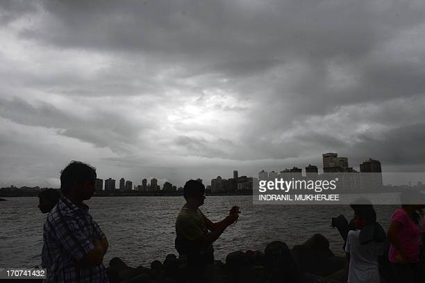 Tourists take photographs as dark monsoon clouds loom overhead along the promenade on Marine Drive in Mumbai on June 17 2013 Heavy rains lashed parts...