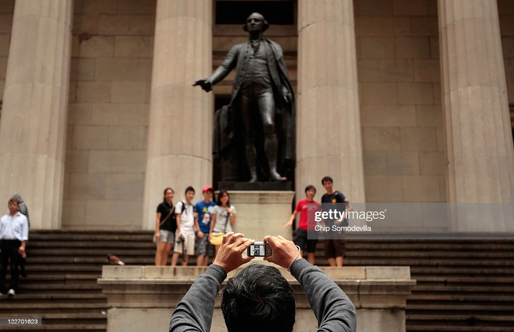 Tourists take photographs as they gradually returned to Lower Manhattan and Wall Street just hours after Hurricane Irene blew through the city August 28, 2011 in New York City. Irene hit New York as a Category 1 hurricane before being downgraded to a tropical storm.