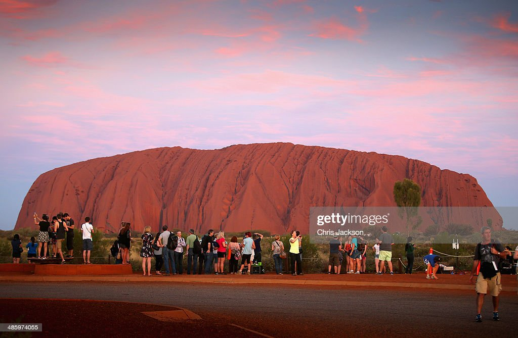 Tourists take photographs at sunset a Uluru ahead of a visit by Prince William, Duke of Cambridge and Catherine, Duchess of Cambridge on April 21, 2014 in Ayers Rock, Australia. The Duke and Duchess of Cambridge are on a three-week tour of Australia and New Zealand, the first official trip overseas with their son, Prince George of Cambridge.