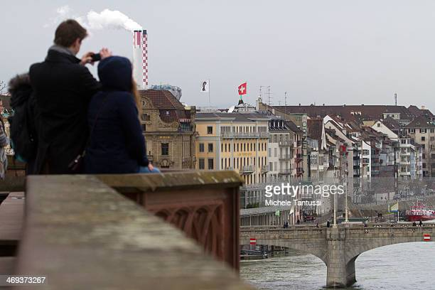 Tourists take Photographs beside the Rhine River on February 14 2014 at BaselSwitzerland Swiss citizens voted with a narrow majority in favour of...