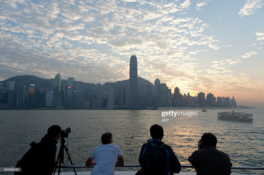 Tourists take photographs from a promenade as commuters travel on the Star Ferry (R) in Victoria Harbour from Hong Kong island (background) to Kowloon (foreground) on November 21, 2013. Hong Kong's economy grew 'moderately' year-on-year in the third quarter as domestic demand and 'resilient' growth in the mainland Chinese market offset a weaker environment in the West, officials said on November 15.
