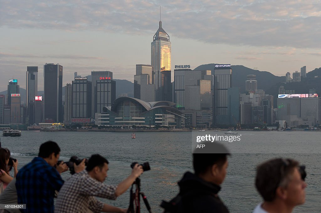 Tourists take photographs from a promenade facing Victoria Harbour and Hong Kong island (background), in Kowloon on November 21, 2013. Hong Kong's economy grew 'moderately' year-on-year in the third quarter as domestic demand and 'resilient' growth in the mainland Chinese market offset a weaker environment in the West, officials said on November 15.