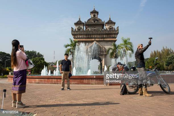 Tourists take photographs in front of the Patuxai Victory monument in Vientiane Laos on Thursday Nov 2 2017 Located in the Mekong region Southeast...