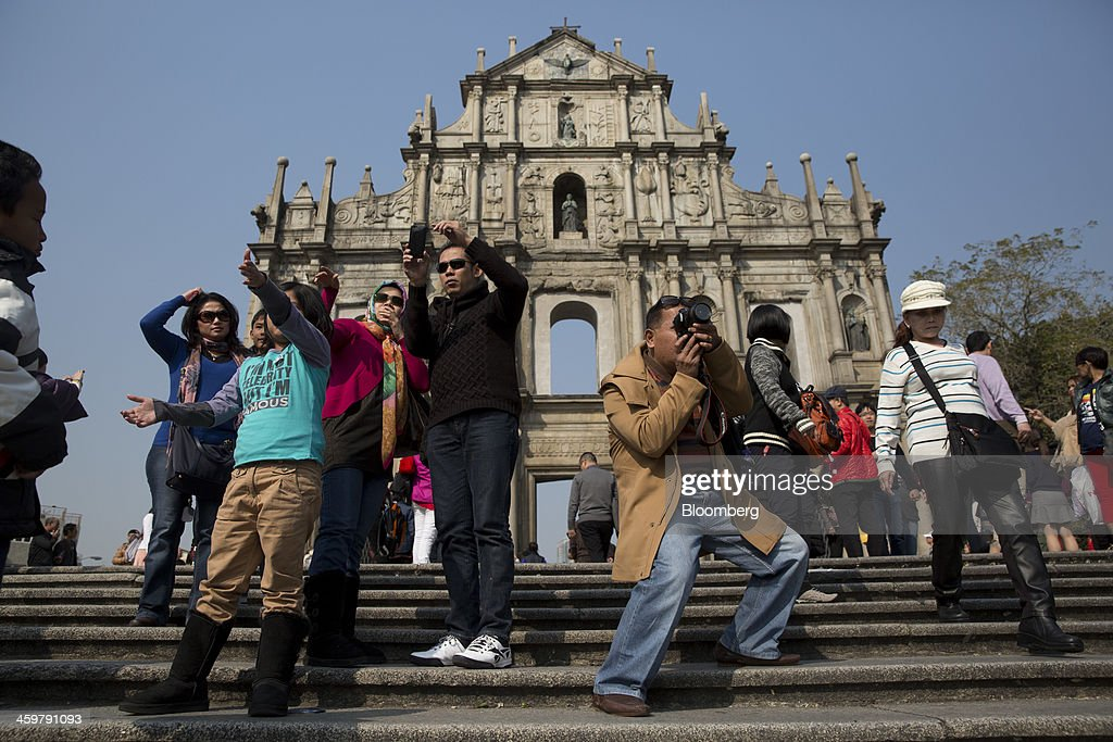 Tourists take photographs in front of the Ruins of St. Paul's Cathedral in Macau, China, on Monday, Dec. 30, 2013. Macau's Gaming Inspection and Coordination Bureau is scheduled to release 2013 revenue figures on Jan. 2. Photographer: Brent Lewin/Bloomberg via Getty Images