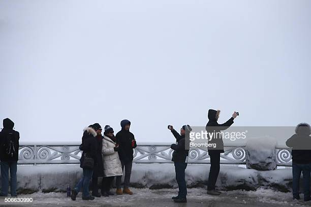 Tourists take photographs in front of the the Horseshoe Falls in Niagara Falls Ontario Canada on Jan 23 2016 A 34 percent plunge in the Canadian...