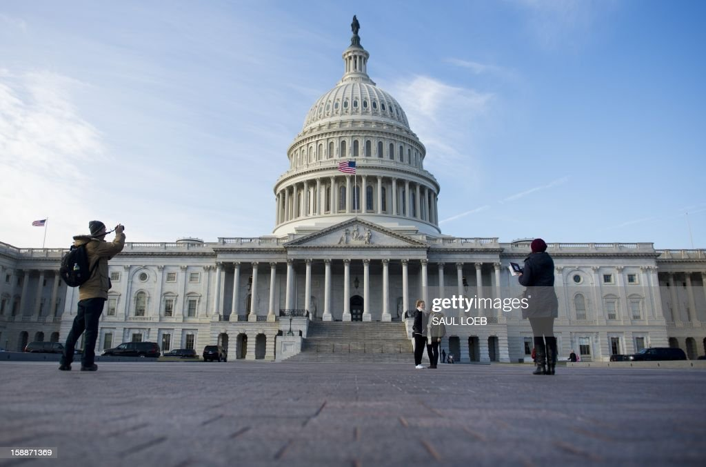 Tourists take photographs in front of the US Capitol in Washington, DC, on January 2, 2013, on the day after a compromise bill passed the US Congress, avoiding the 'fiscal cliff.' The agreement raises taxes on the rich and puts off automatic $109 billion federal budget cuts for two months. AFP PHOTO / Saul LOEB