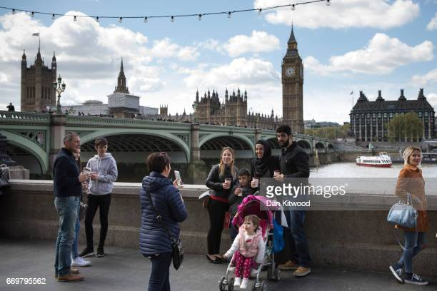 Tourists take photographs near the Houses of Parliament on April 18 2017 in London United Kingdom British Prime Minister Theresa May announced...