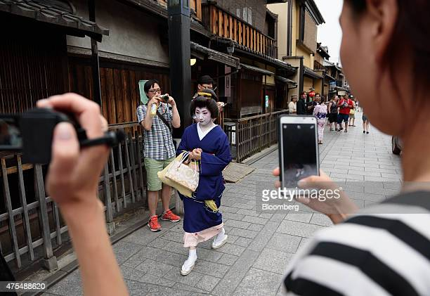 Tourists take photographs of a geiko walking through the Gion area of Kyoto Japan on Thursday May 28 2015 Spending by visitors to Japan jumped to the...