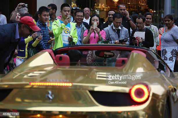 Tourists take photographs of a Gold Ferrari in Knightsbridge on August 8 2014 in London England Tourists and car enthusiasts have been flocking to...
