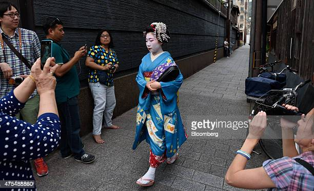 Tourists take photographs of a maiko or apprentice geisha walking through the Gion area of Kyoto Japan on Thursday May 28 2015 Spending by visitors...