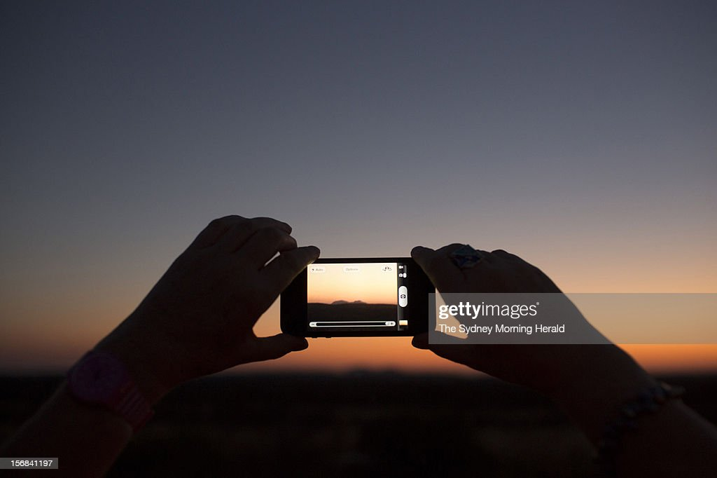 Tourists take photographs of sunset over Kata Tjuta during a sunset dining experience at Uluru in Central Australia, November 5, 2012. (Photo by Glenn Campbell/The Sydney Morning Herald/Fairfax Media via Getty Images).