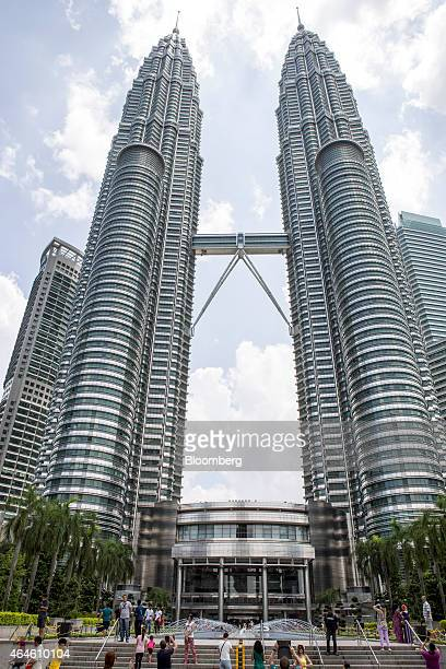 Tourists take photographs of the Petronas Twin Towers in Kuala Lumpur Malaysia on Friday Feb 27 2015 Petronas the Malaysian state oil company...