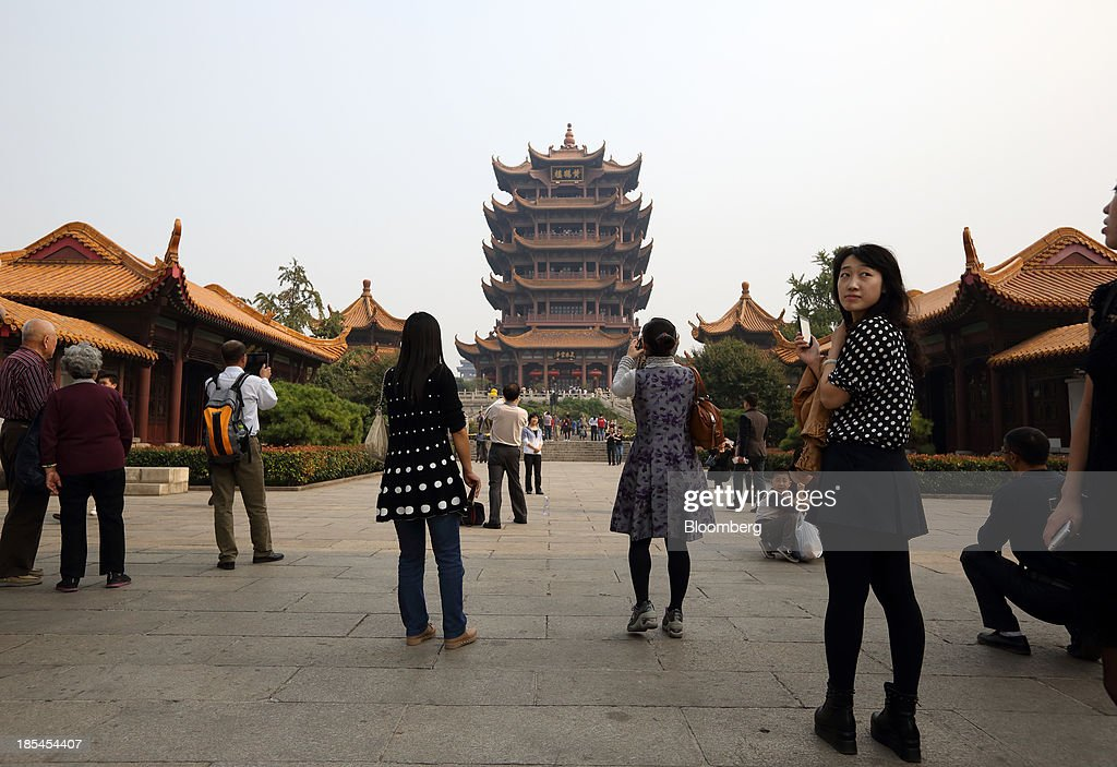 Tourists take photographs of the Yellow Crane Tower in Wuhan, China, on Sunday, Oct. 20, 2013. China's economic expansion accelerated to 7.8 percent in the third quarter from a year earlier, the statistics bureau said Oct. 18, reversing a slowdown that put the government at risk of missing its 7.5 percent growth target for 2013. Photographer: Tomohiro Ohsumi/Bloomberg via Getty Images