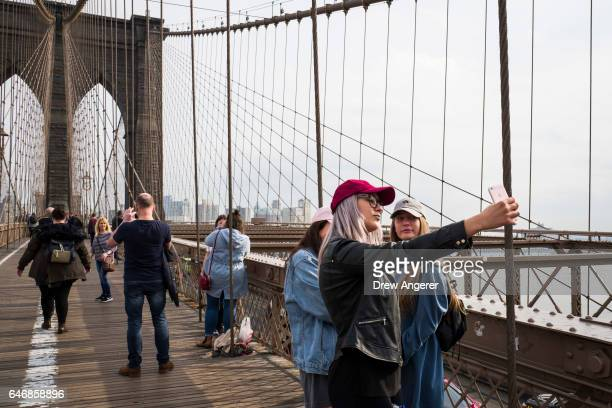 Tourists take photographs on the Brooklyn Bridge March 1 2017 in New York City NYC Company the city's tourism marking agency released a new forecast...