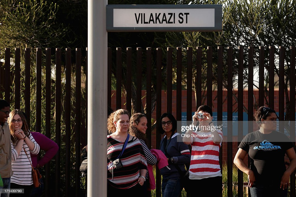 Tourists take photographs outside former President Nelson Mandela's Soweto home, which now serves as a museum, June 24, 2013 in Johannesburg, South Africa. South African President Jacob Zuma confirmed that Mandela's condition has become critical since he was admitted to the hospital over two weeks ago for a recurring lung infection.