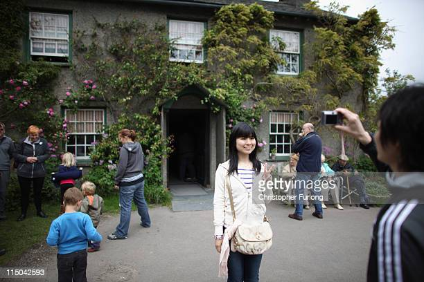 Tourists take photographs outside the home of Beatrix Potter on June 1 2011 in Sawrey United Kingdom The English Lake District is on the shortlist of...