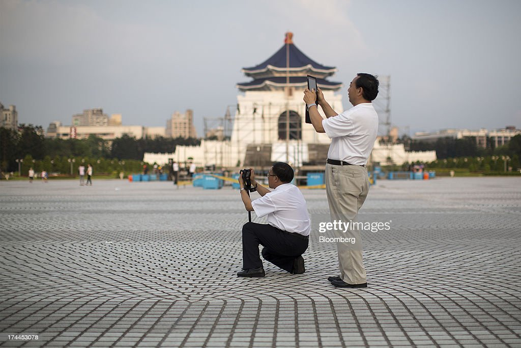Tourists take photographs with a camera, left, and a tablet computer at the Chiang Kai Shek Memorial Hall plaza in Taipei, Taiwan, on Wednesday, July 24, 2013. Taiwan President Ma Ying-jeou ruled out driving down the Taiwan dollar to boost exports following the currencys rally against the yen and said the government still aims for growth of at least 2 percent this year. Photographer: Jerome Favre/Bloomberg via Getty Images